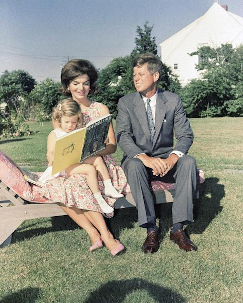 FILE - In this July 25, 1960 file photo , Sen. John F. Kennedy, D-Mass., sits with wife, Jacqueline, as she reads to their daughter, Caroline, at Hyannis Port, Mass. (AP Photo)