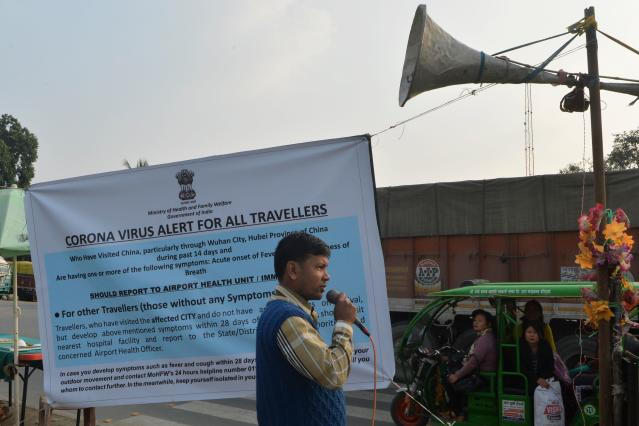 An Indian health worker speaks next to a banner durign a coronavirus information camp for travellers at an India-Nepal border crossing in Siliguri.