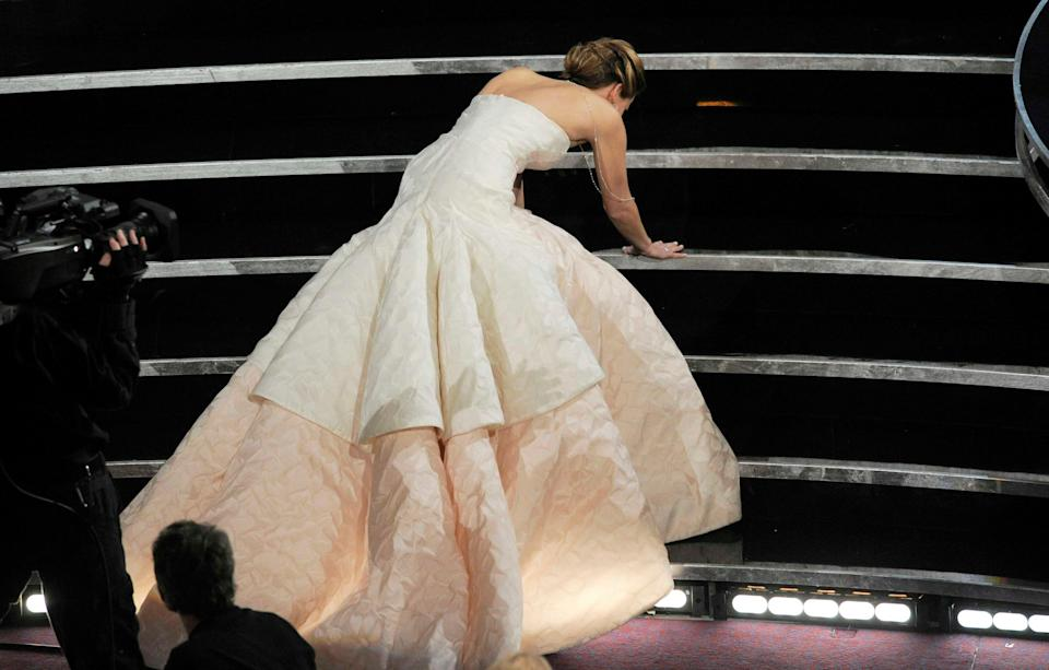 "Jennifer Lawrence trips as she heads to the stage to accept best actress for ""Silver Linings Playbook"" at the Oscars in 2013."