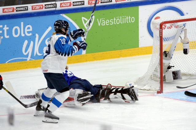 Goalkeeper Alex Rigsby of the United States lies on the ice while Riikka Nieminen of Finland starts celebrating her game-winning overtime goal which was later disallowed during the IIHF Women's Ice Hockey World Championships final match between the United States and Finland in Espoo, Finland, Sunday, April 14, 2019. (Mikko Stig/Lehtikuva via AP)