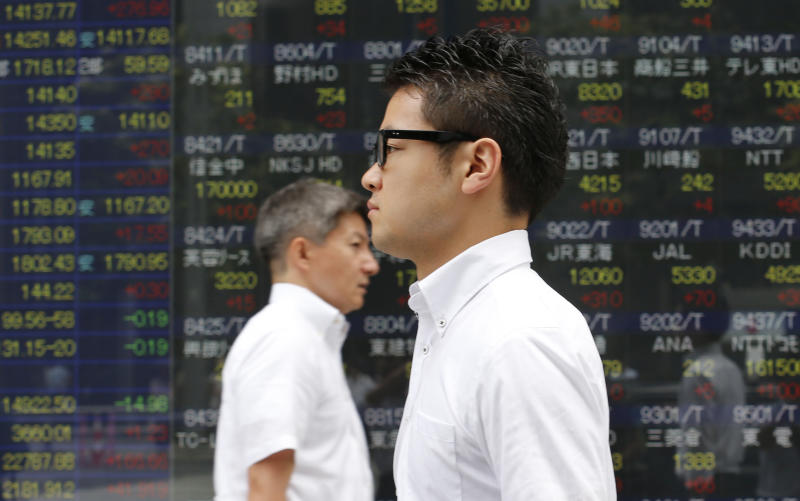 People walk by an electronic stock board of a securities firm in Tokyo, Monday, Sept. 9, 2013. Asian stocks opened higher on Monday, lifted by Tokyo's Olympic bid victory, Chinese export growth and an Australian conservative coalition's election victory. Japanese stocks rallied, with the Nikkei 225 jumping nearly 1.9 percent to 14,122.10, and the yen fell after Tokyo was chosen to host the 2020 Summer Olympics and a revised estimate showed the economy grew faster than previously reported in the second quarter.(AP Photo/Koji Sasahara)