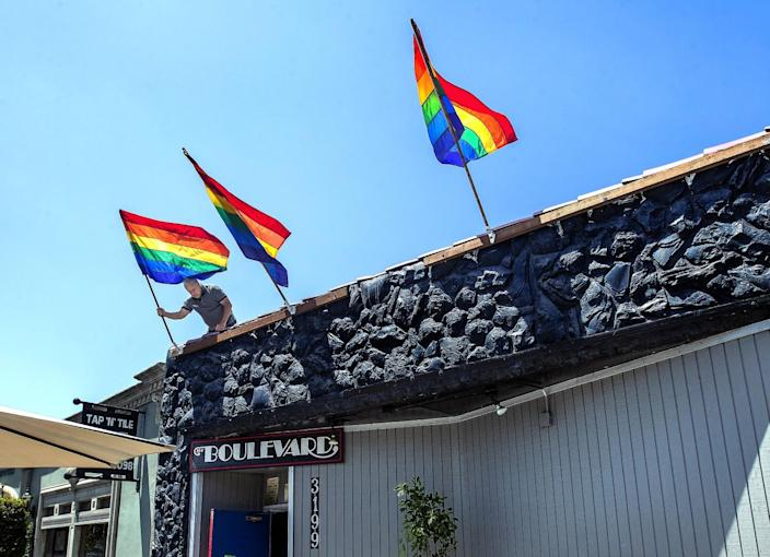 Steve Terradot places rainbow flags in their holders above the front entrance to the Boulevard.
