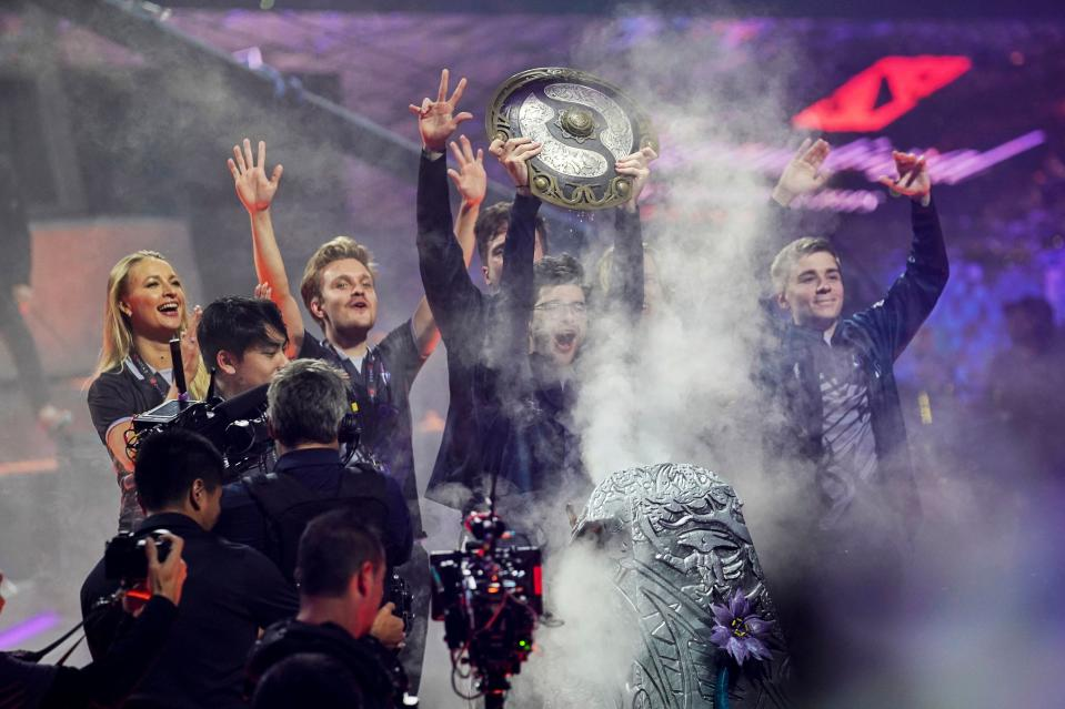 """Sebastien """"Ceb"""" Debs (C) of team OG holds the winner's trophy as the team wins the Dota 2 eSports Best of 5 final match during the International Dota 2 Championships in Shanghai on August 25, 2019. (Photo by STR / AFP) / China OUT (Photo credit should read STR/AFP/Getty Images)"""