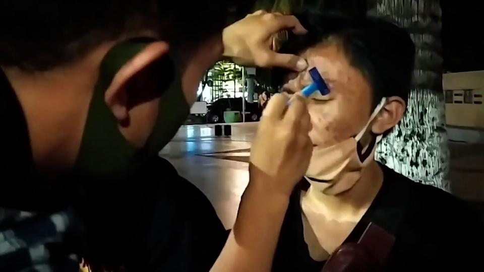 The officers are seen shaving one of the teen's eyebrows off. Source: Viral Press/australscope