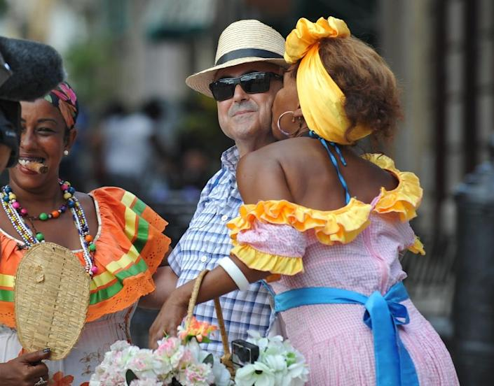 A US tourist is kissed by a Cuban woman clad in typical attire in a street of Old Havana, on September 18, 2015 (AFP Photo/Yamil Lage)