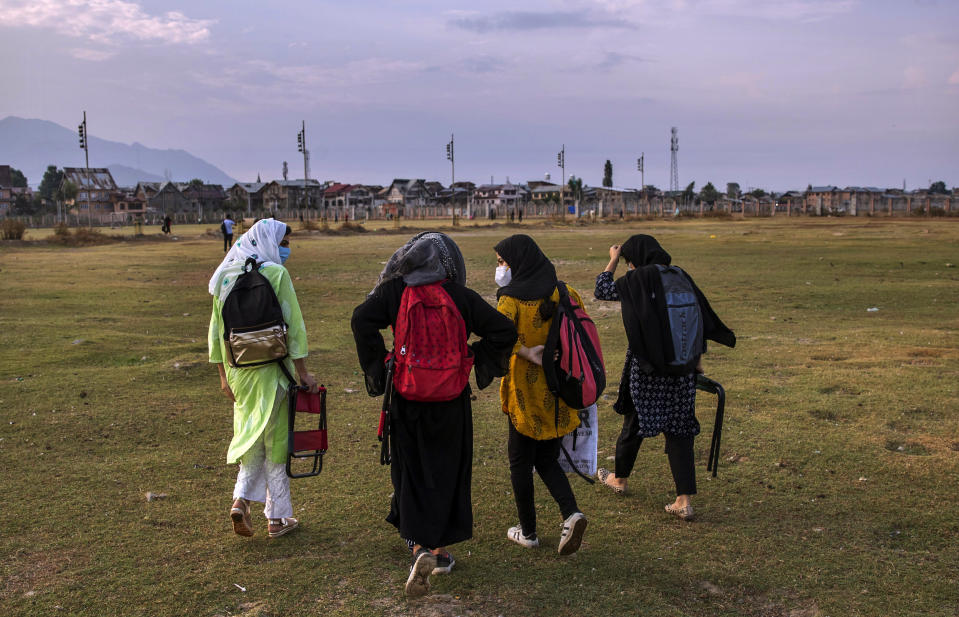 Kashmiri students walk homeward after attending an open-air class inside Eidgah, a ground reserved for Eid prayers, in Srinagar, Indian controlled Kashmir, Friday, July 31, 2020. When months went by without teaching, Muneer Alam, an engineer-turned-math teacher, started the informal community school in the form of an open-air classroom in June. Schools in the disputed region reopened after six months in late February, after a strict lockdown that began in August 2019, when India scrapped the region's semi-autonomous status. In March schools were shut again because of the coronavirus pandemic. (AP Photo/Dar Yasin)