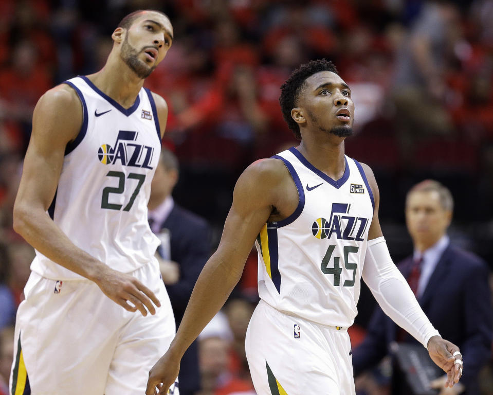 Utah Jazz guard Donovan Mitchell (45) and center Rudy Gobert look at the scoreboard during a timeout during the second half of Game 1 of an NBA basketball first-round playoff series against the Houston Rockets, Sunday, April 14, 2019, in Houston. Houston won the game 122-90. (AP Photo/Eric Christian Smith)
