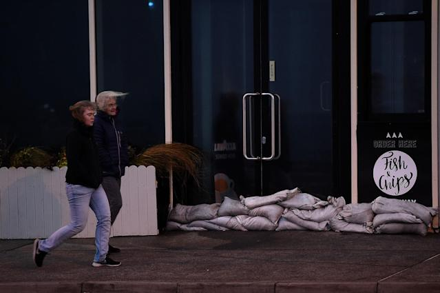 <p>People walk past a sandbagged chip shop during Storm Ophelia in Galway, Ireland, Oct.16, 2017. (Photo: Clodagh Kilcoyne/Reuters) </p>