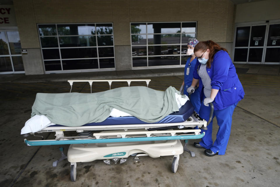 Medical staff pause as they move the body of a COVID-19 patient who died to a loading dock to hand off to a funeral home van, at the Willis-Knighton Medical Center in Shreveport, La., Wednesday, Aug. 18, 2021. (AP Photo/Gerald Herbert)