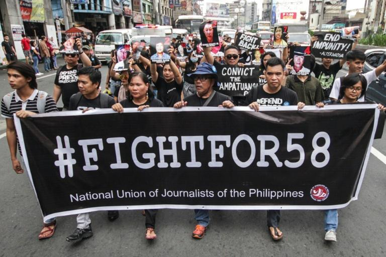 Journalists take part in a protest outside the presidential palace in Manila to commemorate the tenth anniversary of the Philippines' worst political massacre where 58 people, including 32 media workers, were slaughtered and dumped in roadside pits