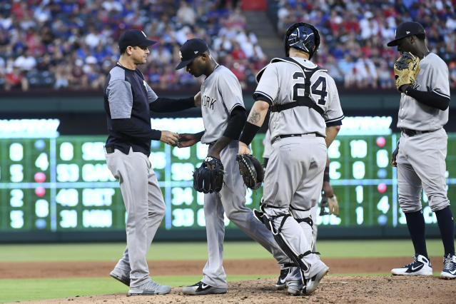 New York Yankees starting pitcher Domingo German hands the ball to manager Aaron Boone as he is pulled from the baseball game against the Texas Rangers in the fourth inning, as catcher Gary Sanchez (24) and shortstop Didi Gregorius, right, stand on the mound Tuesday, May 22, 2018, in Arlington, Texas. (AP Photo/Jeffrey McWhorter)