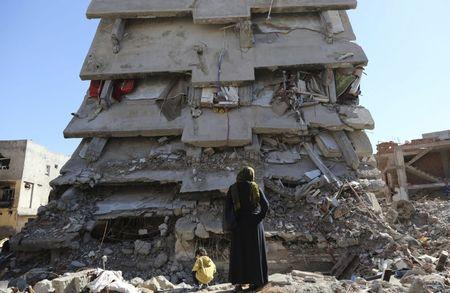 A woman looks at a building, which was damaged during the security operations and clashes between Turkish security forces and Kurdish militants, in the southeastern town of Cizre in Sirnak province