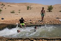 Palestinians cool down in a water canal in the Jordan Valley village of Al-Auja, in the occupied West Bank (AFP/MENAHEM KAHANA)