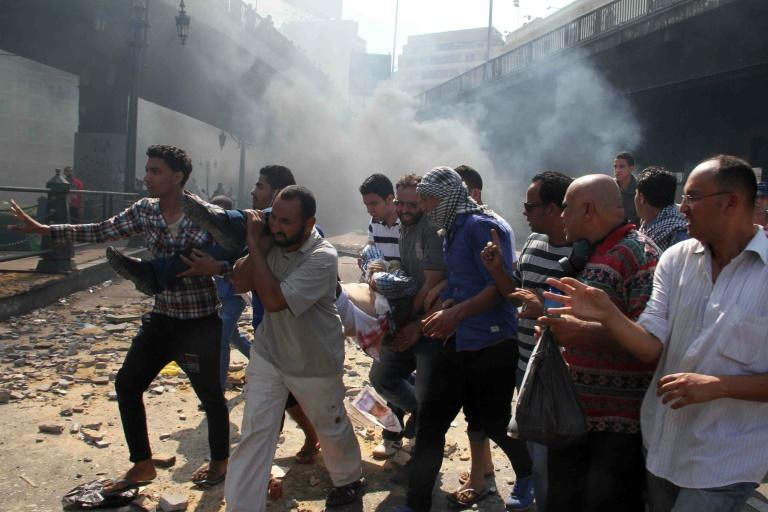 Egyptian Muslim Brotherhood supporters carry a wounded protestor in Cairo's Ramses square on August 16, 2013 after clashes broke out with police during a demonstration in support of Egypt's ousted president Mohamed Morsi