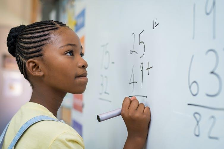 Young girl solving maths problem on whiteboard