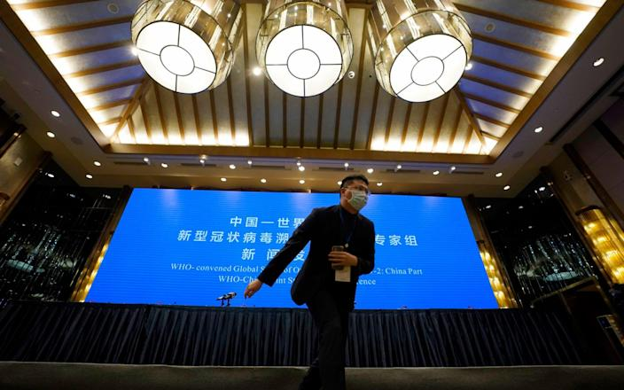 A Chinese journalist walks past the stage set for WHO-China Joint Study Press Conference on the Study of Origins of SARS-CoV-2 held near the end of the World Health Organization mission in Wuhan - Ng Han Guan/AP