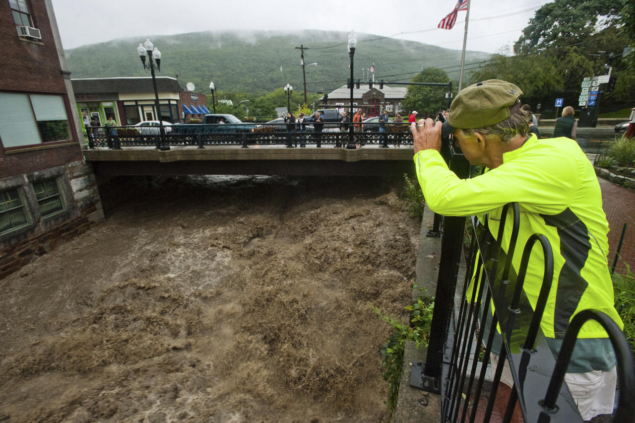 Mel Martin joins a crowd watching the raging Whetstone Brook surge over the falls in downtown Brattleboro, Vt. on Sunday, Aug. 28, 2011. The remnants of Hurricane Irene dumped torrential rains on Vermont on Sunday, flooding rivers and closing roads from Massachusetts to the Canadian border, putting parts of two towns underwater and leaving one young woman swept away and feared drowned in the Deerfield River. (AP Photo/The Brattleboro Reformer, Chris Bertelsen)