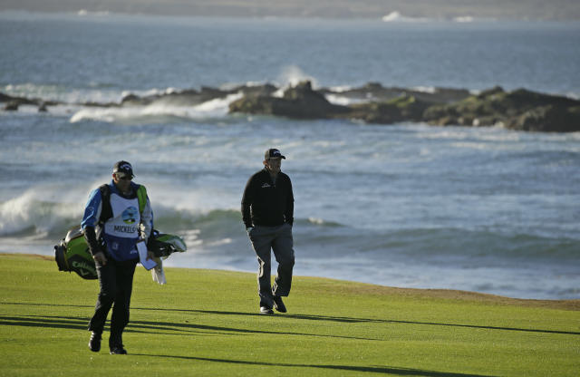 Phil Mickelson walks up the 18th fairway of the Pebble Beach Golf Links with his brother and caddie Tim Mickelson during the final round of the AT&T Pebble Beach Pro-Am golf tournament Monday, Feb. 11, 2019, in Pebble Beach, Calif. Mickelson won the tournament after finishing at 19-under-par. (AP Photo/Eric Risberg)