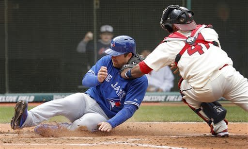 Toronto Blue Jays' Adam Lind slides safely into home, beating the tag by Cleveland Indians catcher Carlos Santana in the fourth inning of a baseball game in Cleveland on Sunday, April 8, 2012. Lind scored on a sacrifice fly by Brett Lawrie. (AP Photo/Amy Sancetta)