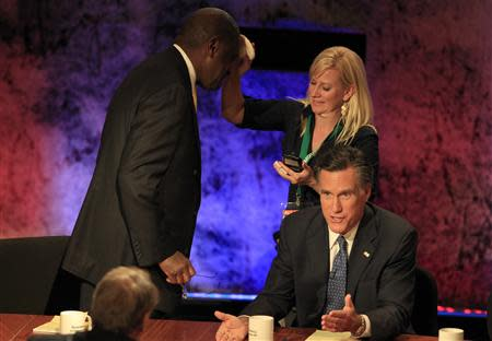 A makeup artist applies powder to the head of Republican presidential candidate businessman Herman Cain as former Massachusetts Governor Mitt Romney talks with debate moderator Charlie Rose during a break in the Republican presidential debate at Dartmouth College in Hanover, New Hampshire October 11, 2011. REUTERS/Adam Hunger