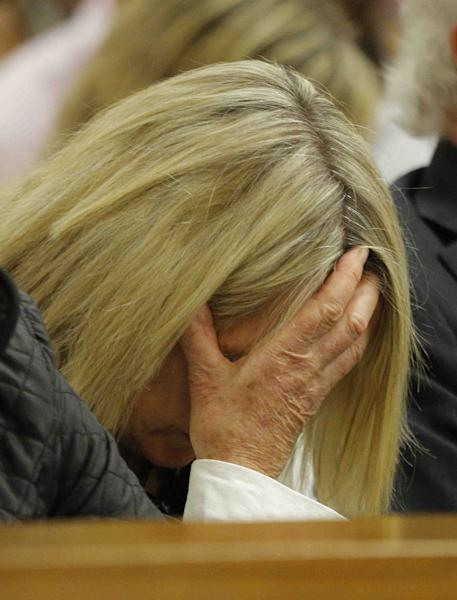 June Steenkamp, center, mother of the late Reeva Steenkamp, reacts as she listens as Oscar Pistorius breaks down during testimony in court in Pretoria, South Africa, Tuesday, April 8, 2014. Pistorius is charged with the murder of his girlfriend Reeva Steenkamp, on Valentines Day in 2013. (AP Photo/Kim Ludbrook, Pool)