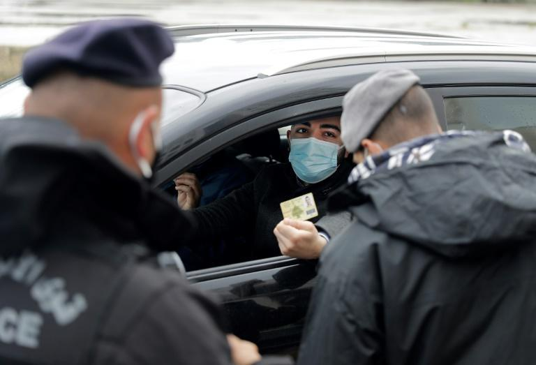 Policemen control a car at a checkpoint in the capital Beirut as Lebanon enters its first day of strict lockdown imposed by the authorities to stem a surge in coronavirus cases