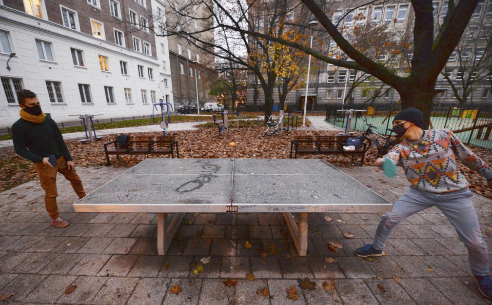 Two men play table tennis in a city square in Warsaw, Poland, Saturday, Nov. 7, 2020. Due to the increase in coronavirus cases, the government introduced new restrictions in shops, schools and cultural institutions through November. (AP Photo/Czarek Sokolowski)