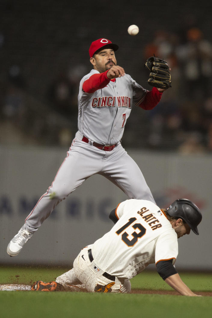 Cincinnati Reds shortstop Eugenio Suárez (7) throws over San Francisco Giants' Austin Slater (13) to complete a double play during the sixth inning of a baseball game, Monday, April 12, 2021, in San Francisco, Calif. Giants pinch hitter Alex Dickerson was out at first. (AP Photo/D. Ross Cameron)