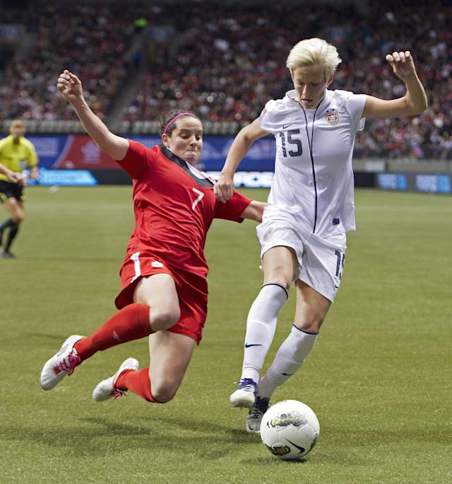 VANCOUVER, CANADA - JANUARY 29: Rhian Wilkinson #7 of Canada makes a sliding tackle to knock the ball away from Mega Rapinoe #15 of the United States during second half of championship action of the 2012 CONCACAF Women's Olympic Qualifying Tournament at BC Place on January 29, 2012 in Vancouver, British Columbia, Canada. (Photo by Rich Lam/Getty Images)