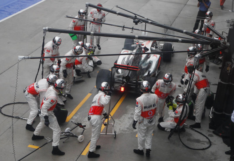 McLaren Formula One driver Jenson Button of Britain leaves pit lane after his car was repaired by his pit crew following a collision during the Malaysian Formula One Grand Prix at Sepang, Malaysia, Sunday, March 25, 2012. (AP Photo/Mark Baker)