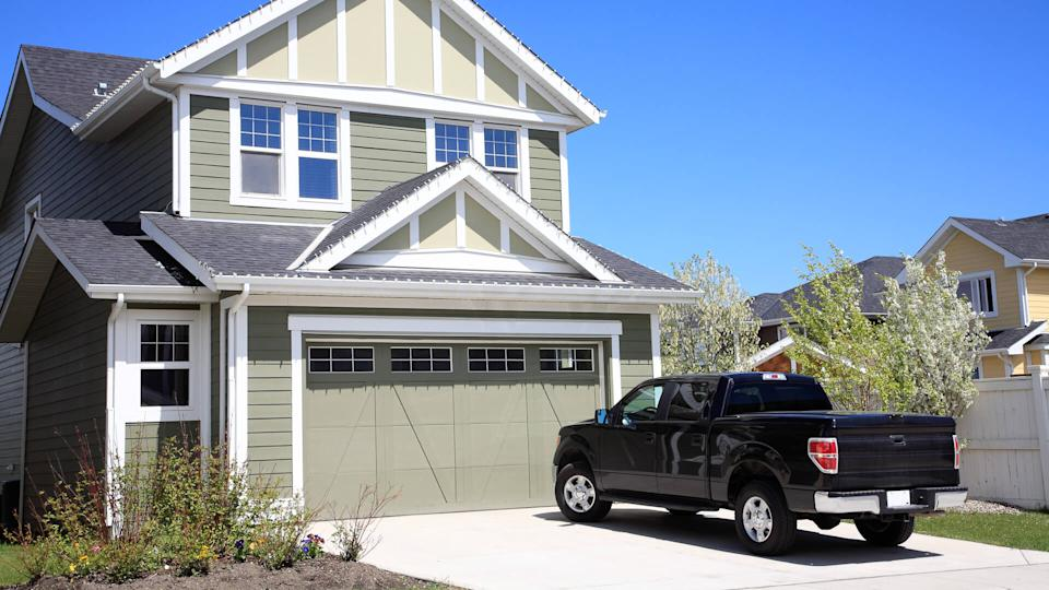 Pretty new two storey home with 4X4 truck parked in driveway.