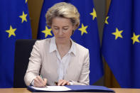 European Commission President Ursula von der Leyen signs the EU-UK Trade and Cooperation Agreement at the European Council headquarters in Brussels, Wednesday, Dec. 30, 2020. European Union's top officials have formally signed the post-Brexit trade deal sealed with the United Kingdom. European Commission president Ursula von der Leyen and European Council president Charles Michel put pen to paper on Wednesday morning during a brief ceremony in Brussels (Johanna Geron, Pool Photo via AP)