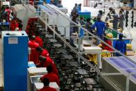 Employees work at an assembly line at a Bata shoe factory in Abuja