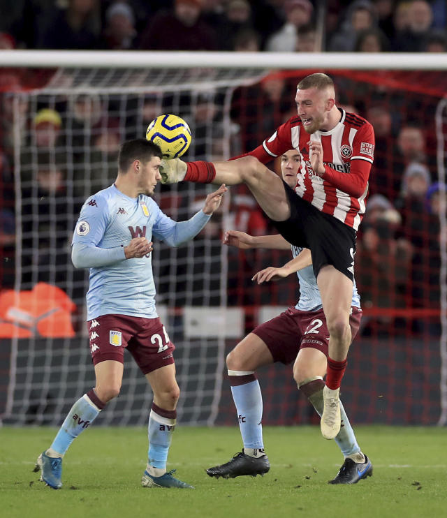 Aston Villa's Frederic Guilbert appears to get kicked in the head by Sheffield United's Oliver McBurnie as he challenges for the ball, during the English Premier League soccer match between Sheffield United and Aston Villa, at Bramall Lane, in Sheffield, England, Saturday, Dec. 14, 2019. (Mike Egerton/PA via AP)