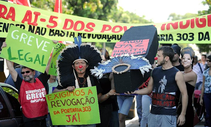 Brazilian natives and employees of the National Indian Foundation protest against the government's decision to authorize actions inside indigenous lands without the natives' permission on July 26, 2012 (AFP Photo/Pedro Ladeira)