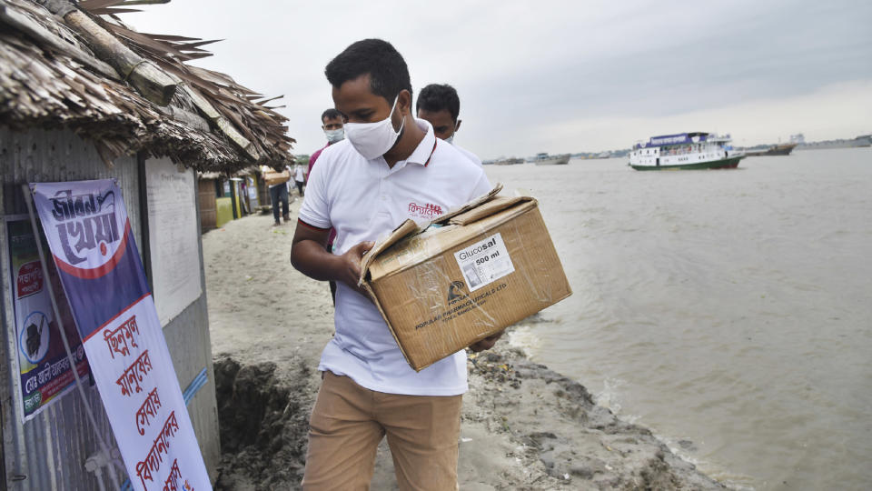 In this photo provided by Bidyanondo Foundation, a health worker arrives in a village with supplies at Banishanta near Mongla seaport in southwestern region of Bangladesh, on Sept. 1, 2020. A Bangladeshi charity has set up a floating hospital turning a small tourist boat into a healthcare facility to provide services to thousands of people affected by this year's devastating floods that marooned millions. (Bidyanondo Foundation via AP)