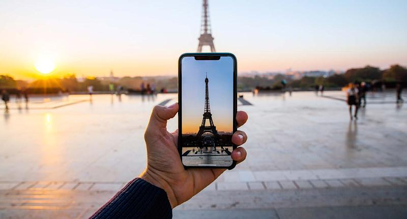 A man takes a photo on his phone of the Eiffel Tower in Paris.