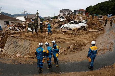 Rescue workers and Japan Self-Defense Force soldiers search for missing people at a landslide site after heavy rain in Kumano Town, Hiroshima Prefecture, western Japan, July 11, 2018. REUTERS/Issei Kato