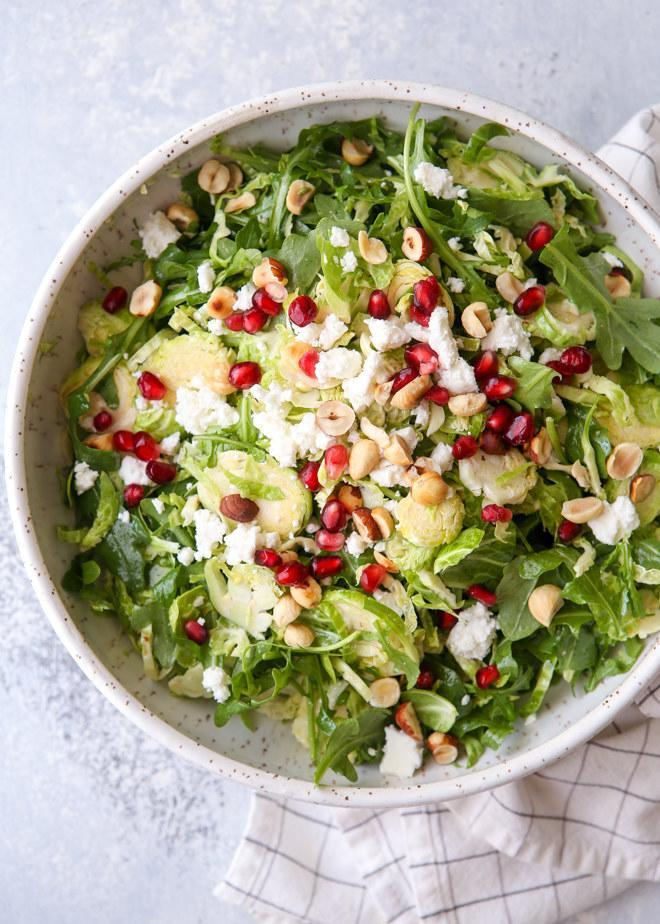 A bowl of arugula and Brussels sprouts salad topped with feta, hazelnuts, and pomegranate seeds.