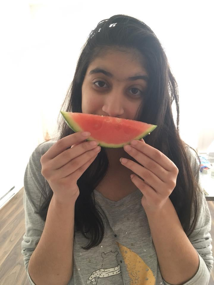 woman holding up a piece of watermelon in front of her mouth