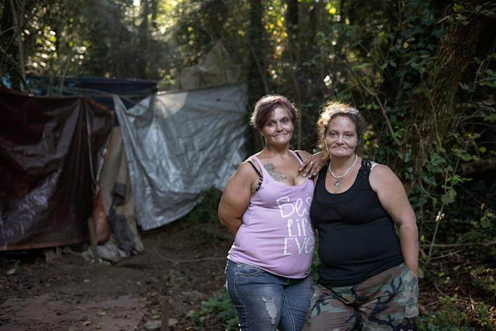 """Flora Harlow and Kat Ryan-Butts stand for a portrait near their tents Sept. 9 in Athens, Ga. Harlow and Ryan-Butts are often referred to as the """"queens"""" of Cooterville because they are known throughout their small encampment as someone you go to when you're in need."""