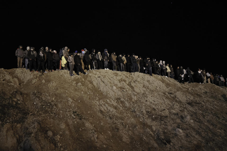 Migrants stand by the border fence as they attempt to get into the U.S. side to San Diego, Calif., from Tijuana, Mexico, Tuesday, Jan. 1, 2019. Discouraged by the long wait to apply for asylum through official ports of entry, many migrants from recent caravans are choosing to cross the U.S. border wall and hand themselves in to border patrol agents. (AP Photo/Daniel Ochoa de Olza)