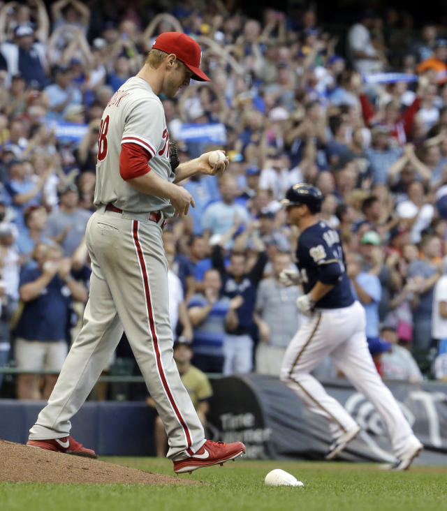 Philadelphia Phillies starting pitcher Kyle Kendrick looks down after giving up a grand slam to Milwaukee Brewers' Lyle Overbay, right, during the first inning of a baseball game Tuesday, July 8, 2014, in Milwaukee. (AP Photo/Morry Gash)