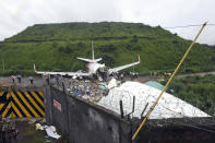 Officials stand by the debris of the Air India Express flight that skidded off a runway while landing in Kozhikode, Kerala state, India, Saturday, Aug. 8, 2020. The special evacuation flight bringing people home to India who had been trapped abroad because of the coronavirus skidded off the runway and split in two while landing in heavy rain killing more than a dozen people and injuring dozens more. (AP Photo/Shijith Sreedhar)
