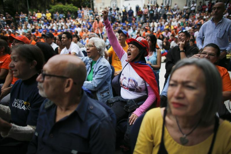 A woman screams in support of opposition leader and self-proclaimed interim President Juan Guaidó during a citizen assembly held at a square in the neighborhood of El Paradiso in Caracas, Venezuela, Monday, Sept. 30, 2019. On Monday, Guaidó came out in defense of the Colombian government claim that Colombian guerrilla troops are operating in Venezuela, and accused Venezuelan President Nicolas Maduro of supporting them. (AP Photo/Ariana Cubillos)