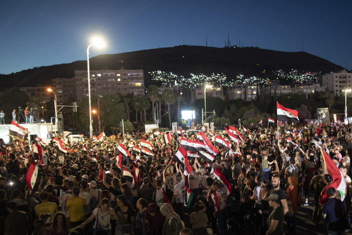 Syrian President Bashar Assad supporters hold up national flags and pictures of Assad they celebrate at Omayyad Square, in Damascus, Syria, Thursday, May 27, 2021. (AP Photo/Hassan Ammar)
