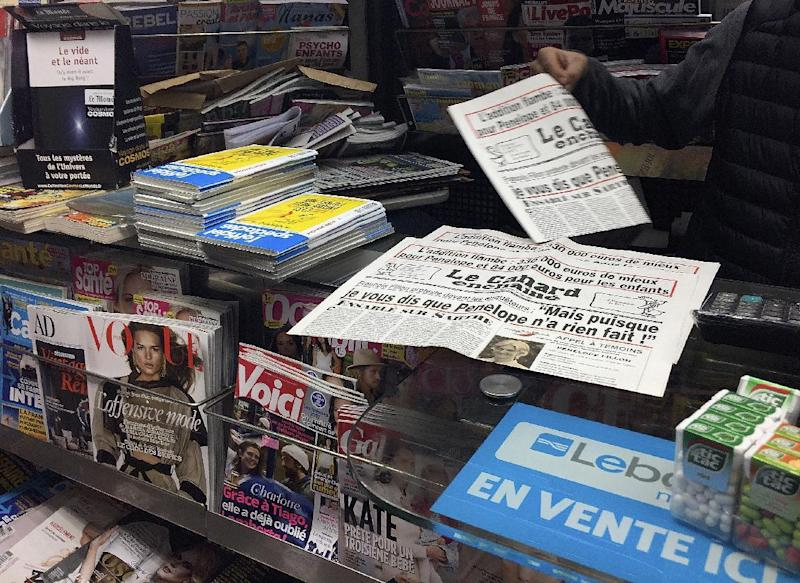 """A newsstand owner picks up a copy of the satirical newspaper Canard Enchaine, or """"The Chained Duck"""" in Paris, Wednesday, Feb. 1, 2017. The dirt-digging weekly's claims that conservative presidential candidate Francois Fillon's political clout helped secure handsomely paid jobs for his wife, Penelope, and two of their children are the just the latest scoops from the 102-year-old newspaper. (AP Photo/Bertrand Combaldieu)"""