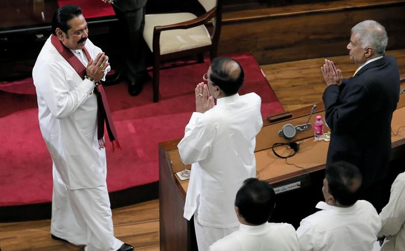 Sri Lanka's former leader Mahinda Rajapaksa, who was appointed as the new Prime Minister, gestures at former Prime Minister Ranil Wickeremesinghe and former President Maithripala Sirisena during the swearing in ceremony in Colombo