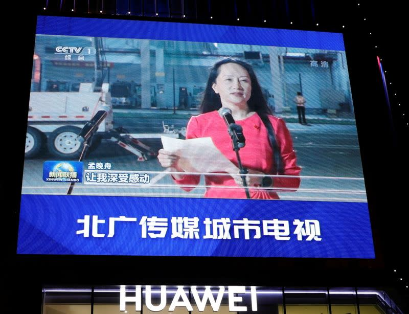 FILE PHOTO: A giant screen on top of a Huawei store shows images of Huawei Technologies Chief Financial Officer Meng Wanzhou, while broadcasting a CCTV state media news bulletin, outside a shopping mall in Beijing