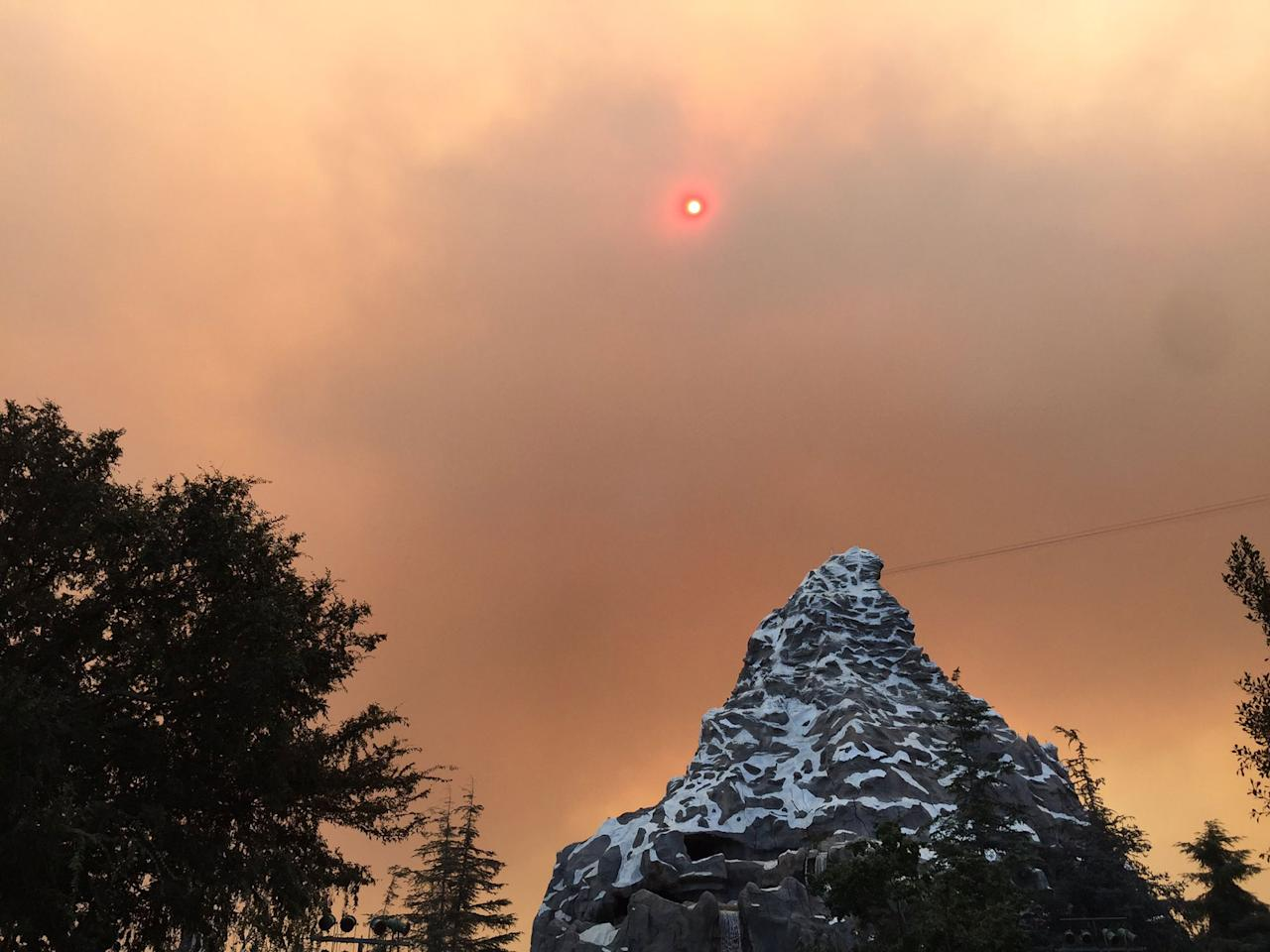 <p>Disneyland and Disney's California Adventure remained open as the skies turned an ominous orange over the Matterhorn ride, seen here. </p>